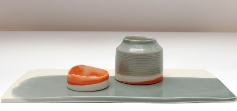 orange and grey vessels on low glazed plinth; porcelain
