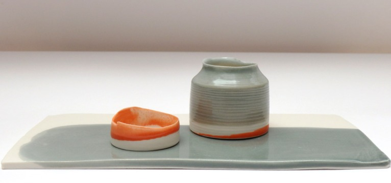 orange and grey vessels on low glazed plinth; porcelain